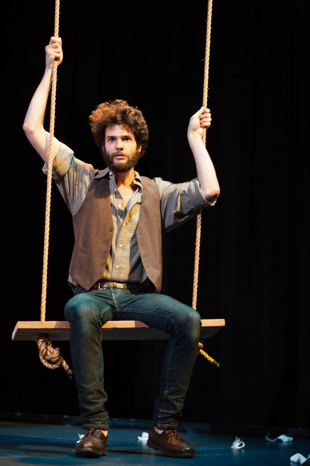 "Con (Adam Magill) contemplates life on the swing."" as description."